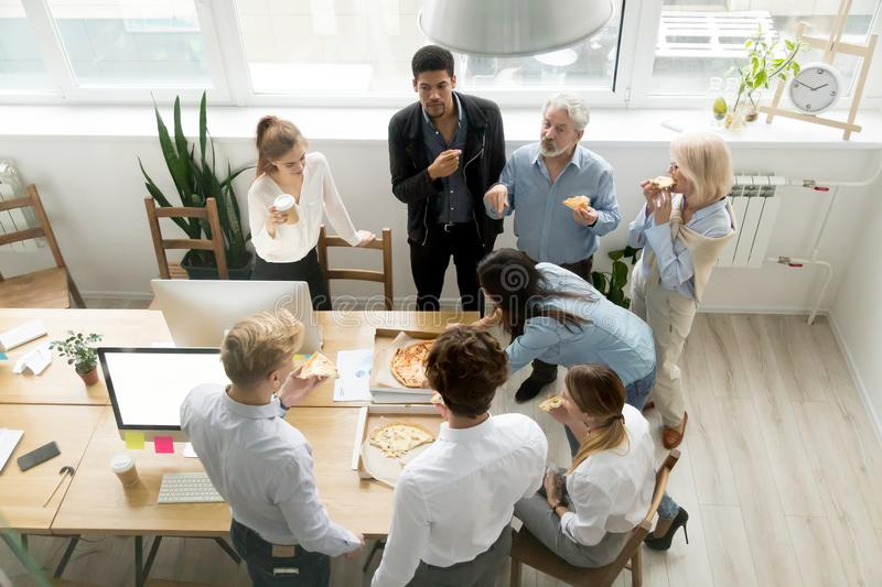 Diverse business team eating pizza together in office, top view. Friendly business team of diverse young and senior people enjoy eating pizza together, employees royalty free stock photo