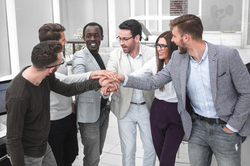 Friendly business team putting their hands together stock photography