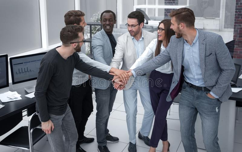 Friendly business team putting their hands together royalty free stock image