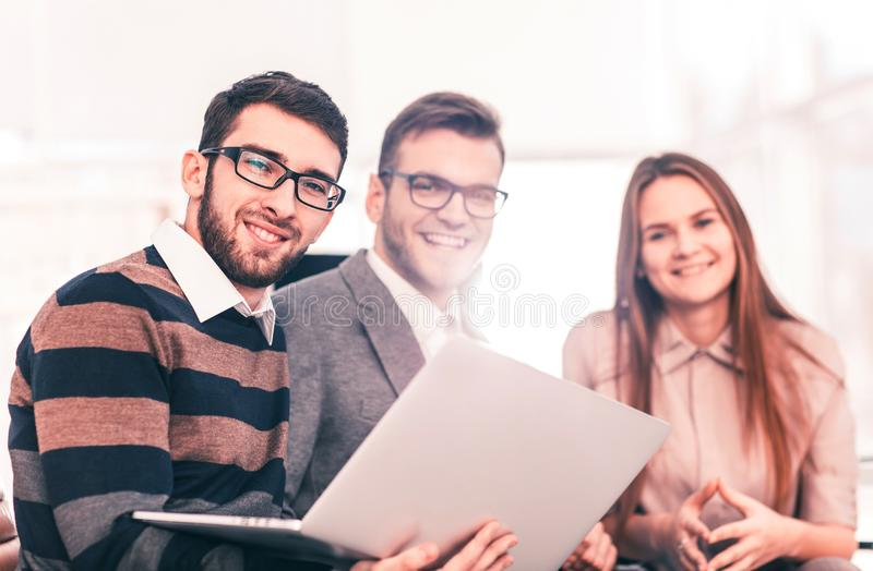 friendly business team working on laptop and discussing business matters royalty free stock photography