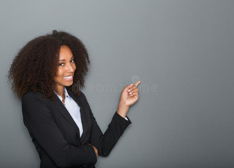 Friendly business woman pointing finger. Close up portrait of a friendly business woman pointing finger on gray background stock images