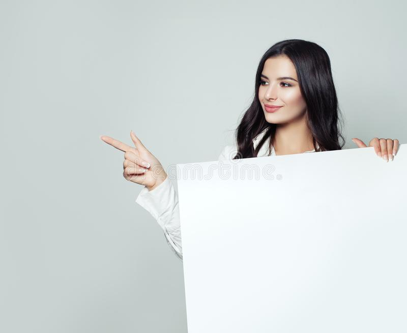 Friendly business woman pointing her finger and showing board stock image