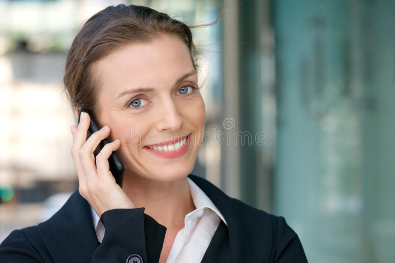 Friendly business woman smiling with mobile phone royalty free stock photos