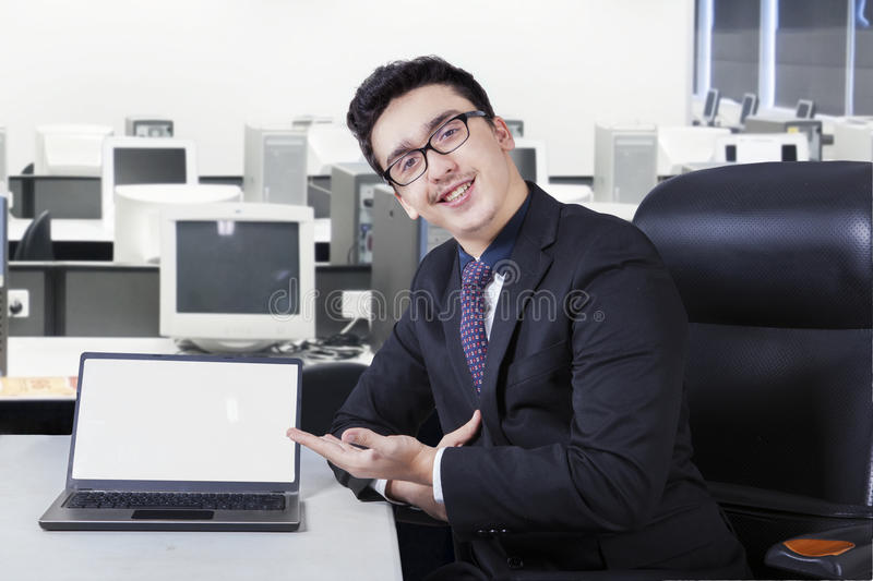 Friendly businessman with empty laptop screen. Portrait of young caucasian businessman showing empty laptop screen in the office stock photography