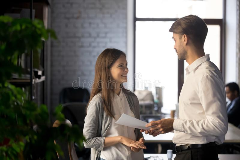 Friendly businessman mentor talking with smiling intern, giving instructions royalty free stock photo
