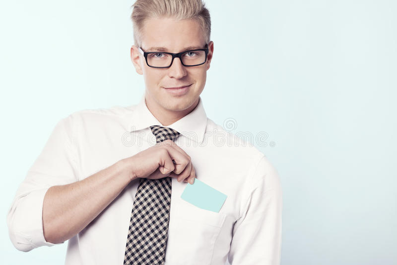 Friendly businessman putting empty card in pocket. stock photo