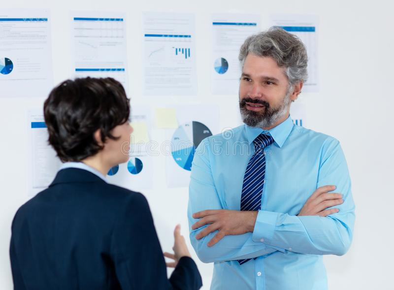 Friendly businessman with tie talking with businesswoman stock photo