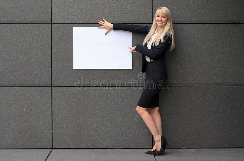 Friendly businesswoman displaying a blank sign royalty free stock photo