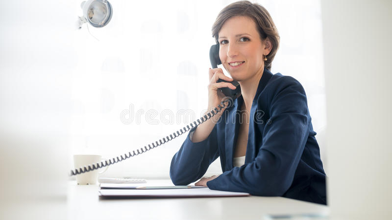 Friendly businesswoman talking on the telephone royalty free stock photography