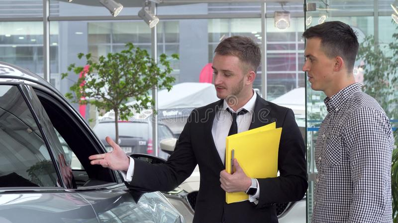 Friendly car dealer helping his male customer choosing automobile to buy royalty free stock image