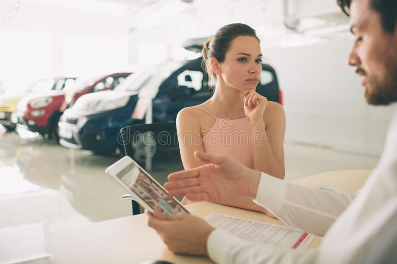 Friendly car salesman talking to a young woman and showing a new car inside showroom Signing of contract. stock photos