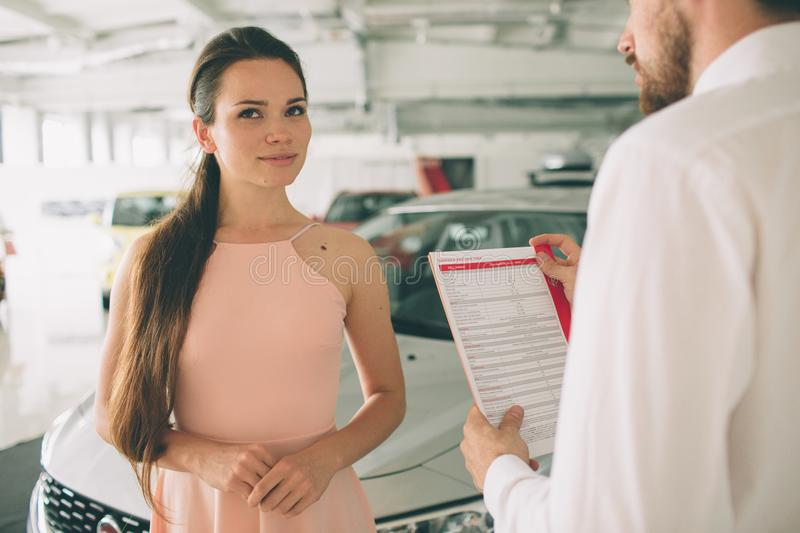 Friendly car salesman talking to a young woman and showing a new car inside showroom Signing of contract. stock image