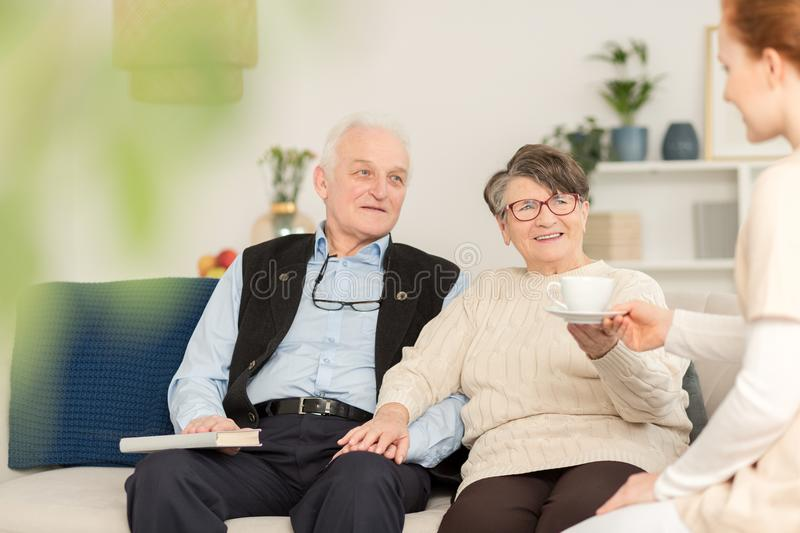 Friendly caregiver and senior couple. Couple of senior people talking to a friendly caregiver stock image