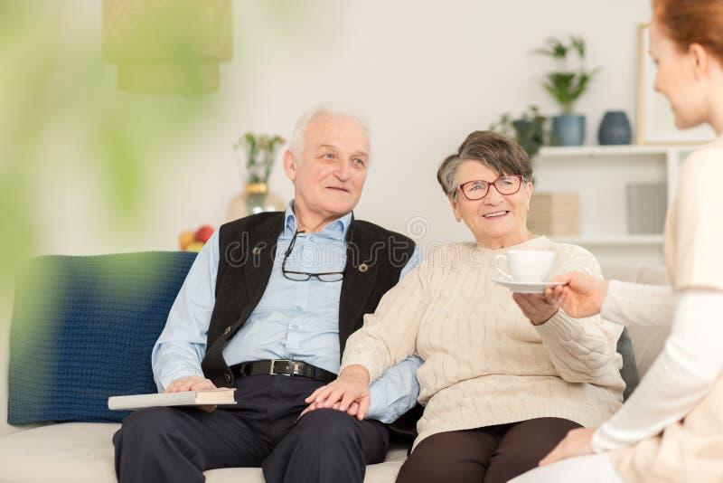 Friendly caregiver and senior couple stock image
