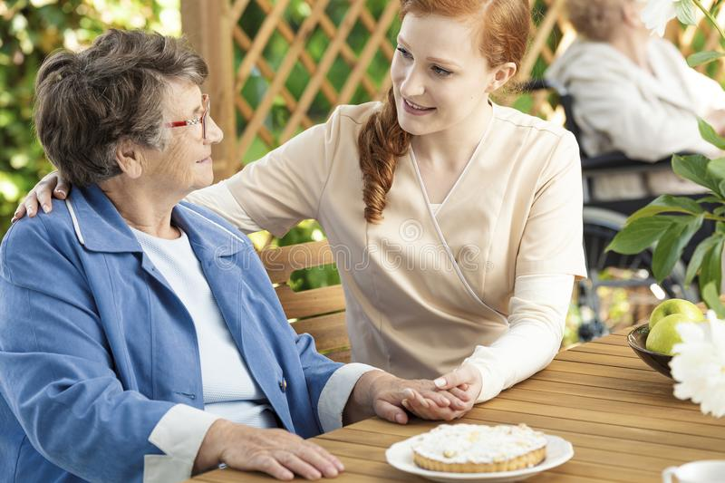 Friendly caregiver supporting happy senior woman during meeting. Friendly caregiver supporting happy senior women during meeting on the terrace royalty free stock photos