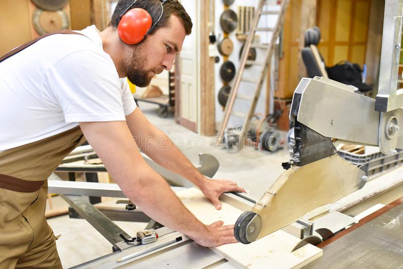 friendly carpenter with ear protectors and working clothes working on a saw in the workshop royalty free stock photography