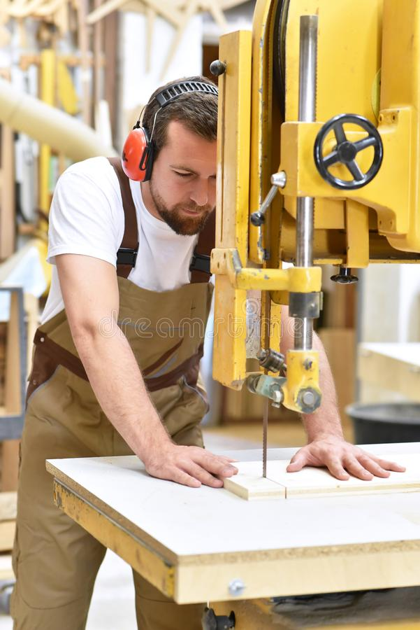 friendly carpenter with ear protectors and working clothes working on a saw in the workshop royalty free stock images