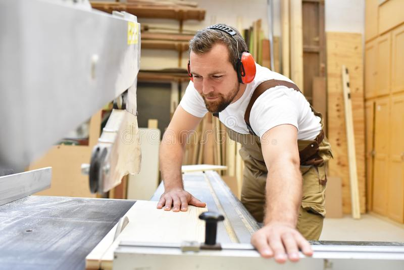 friendly carpenter with ear protectors and working clothes working on a saw in the workshop stock image