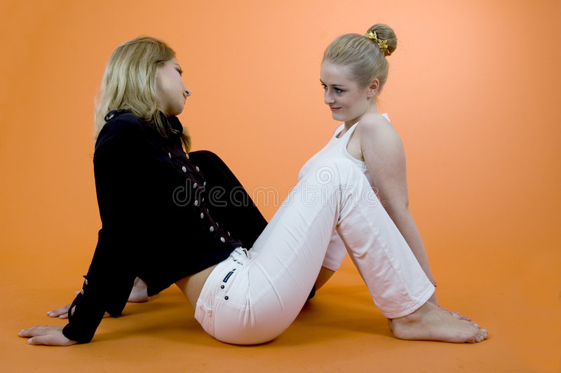 Friendly Chat. Two young women sitting on the floor in opposite directions, side by side. Taken in studio with an orange background stock photos