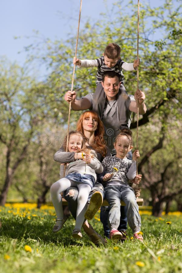 Friendly, cheerful family on a swing in the Park royalty free stock photos