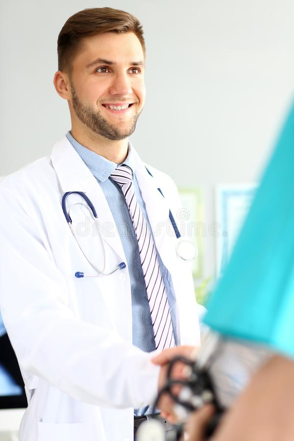 Friendly cheerful doctor. Portrait of smiling specialist looking away with joy and anticipation. Good professional wearing white uniform with stethoscope stock photography