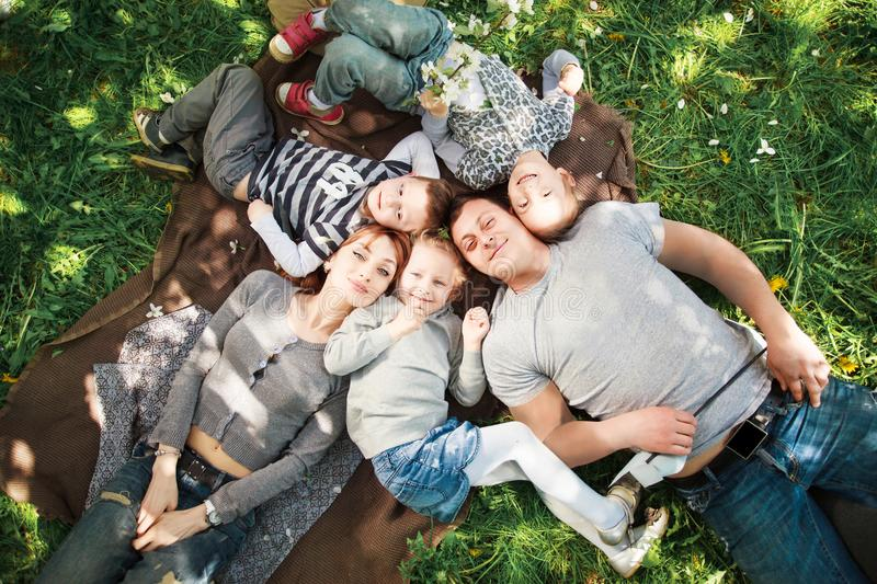 Friendly, cheerful family on a picnic lying on the grass stock photo