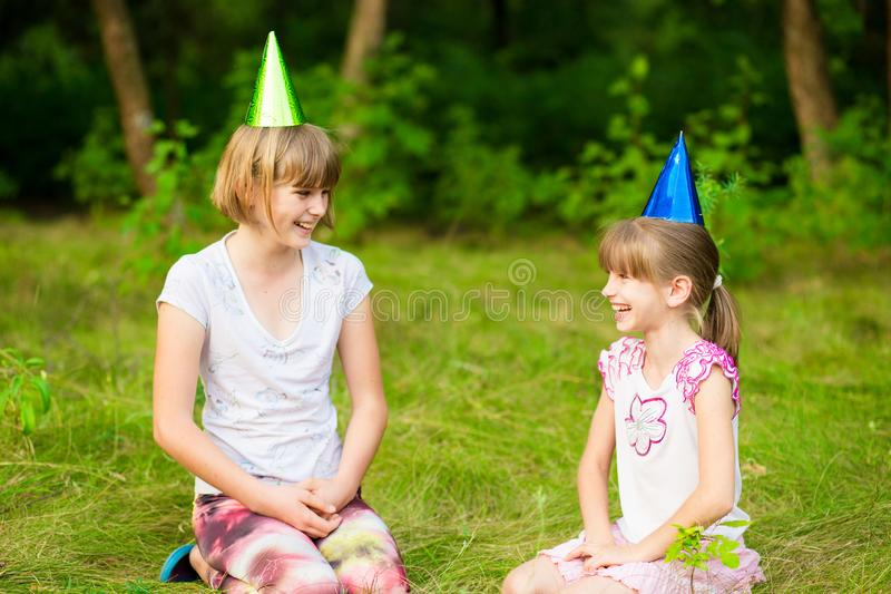 Friendly children in festive cone caps, have fun together as celebrate birthday look with happy expressions at camer royalty free stock image