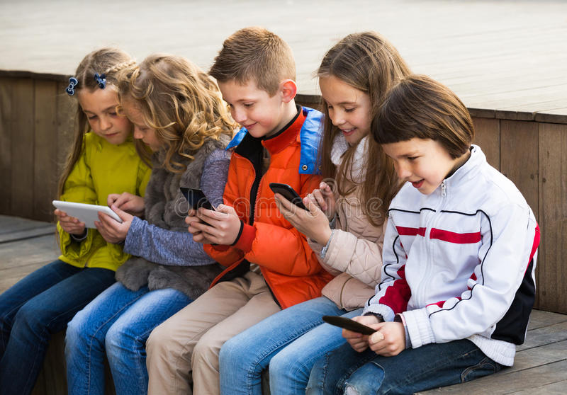Friendly children sitting with mobile devices royalty free stock photography