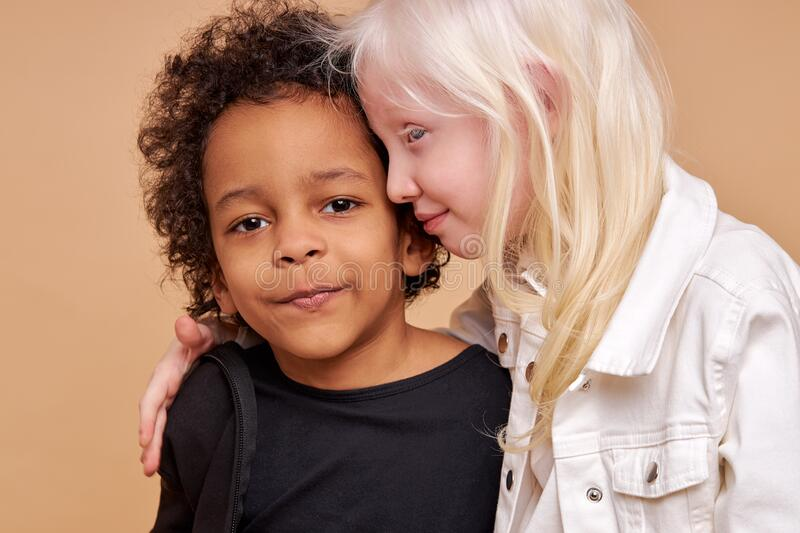 Friendly children, tender black and albino kids. Portrait of friendly children, tender black and albino kids standing close to each other. lovely girl with stock photography