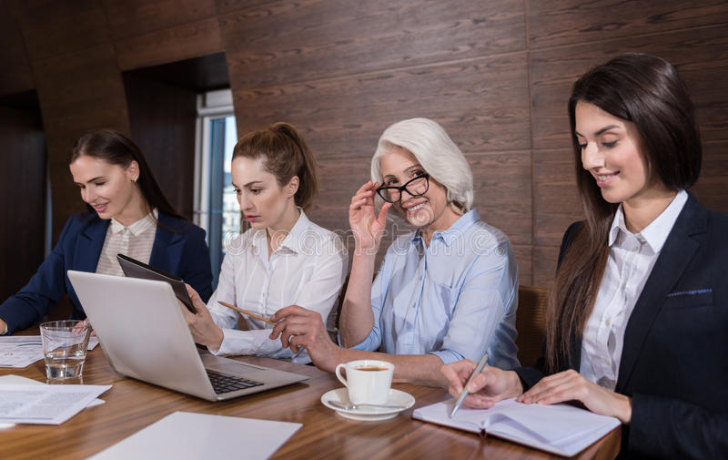 Friendly colleagues doing their job in office. Look at us. Friendly delighted female colleagues doing their job and posing while sitting in an office royalty free stock photo