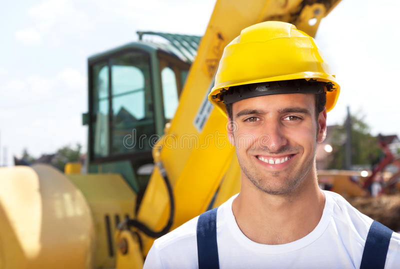 Friendly construction worker in front of his excavator royalty free stock photography
