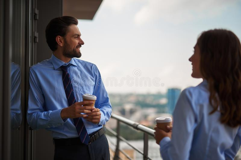 Two colleagues drinking coffee on office balcony royalty free stock photos