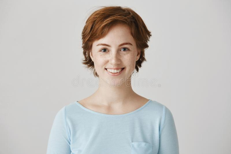 Friendly cute redhead european female colleague with freckles, smiling broadly, standing with confident and happy royalty free stock images