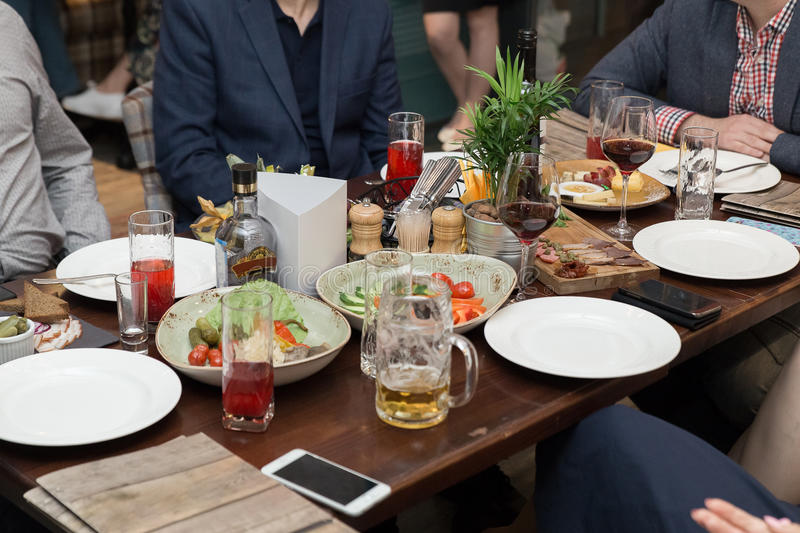 Friendly dinner. group of people having dinner together while sitting at the rustic wooden table royalty free stock image