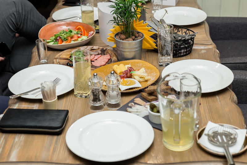 Friendly dinner. group of people having dinner together while sitting at the wooden table royalty free stock images
