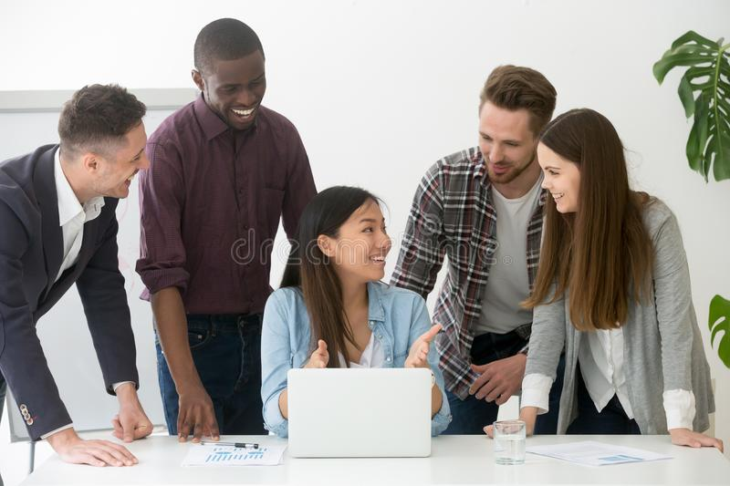 Friendly diverse team working together at laptop in coworking sp. Friendly diverse work team smiling while cooperating working at laptop together, colleagues royalty free stock images
