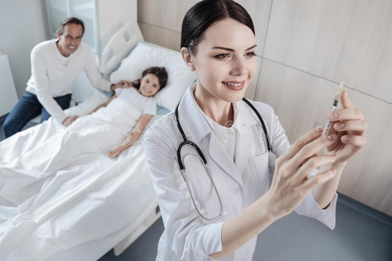 Friendly doctor checking syringe before injection royalty free stock images