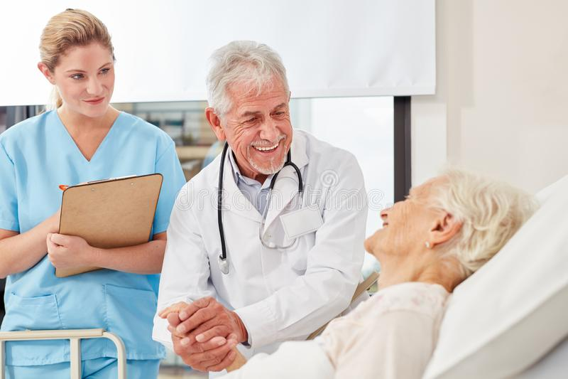 Friendly doctor holds the hand of a senior citizen royalty free stock photo