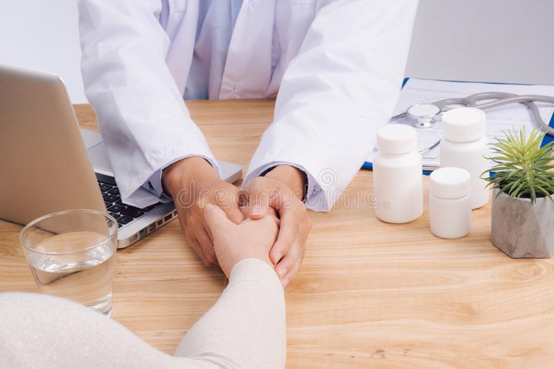 Friendly doctor hands holding patient hand sitting at the desk f royalty free stock photo