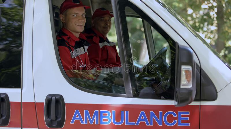 Friendly doctors in ambulance looking at camera, professional emergency service. Stock photo royalty free stock photography