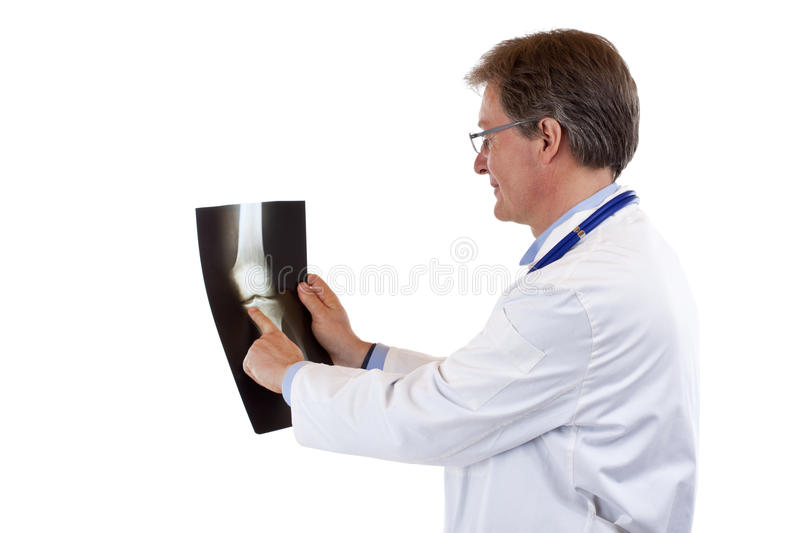 Friendly elderly doctor points to knee x-ray stock photos