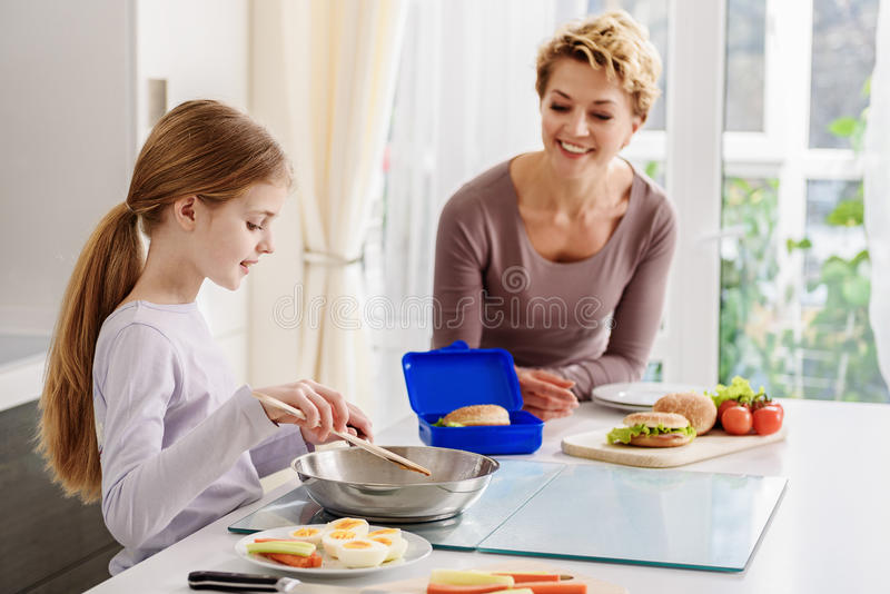 Friendly family cooking breakfast together. Cute girl is frying food on pan in kitchen. She is standing and smiling. Her mother is helping her with enjoyment royalty free stock image