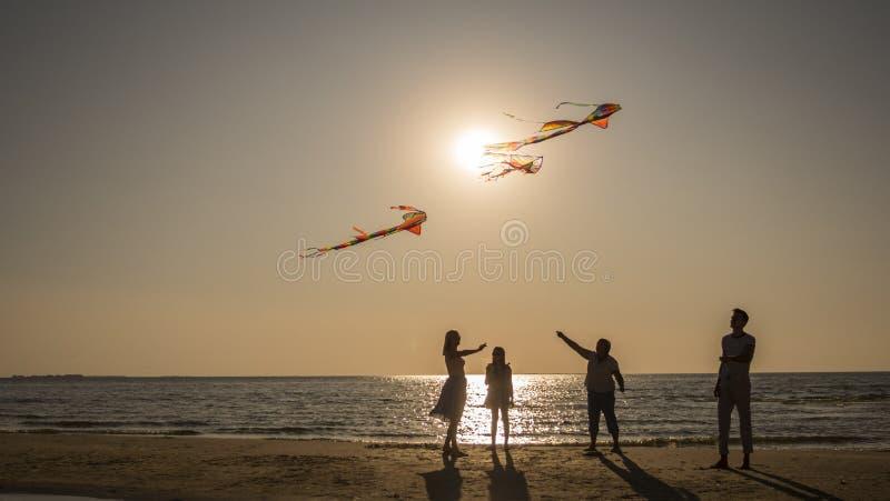 Friendly family plays with kites on the seashore. royalty free stock photos