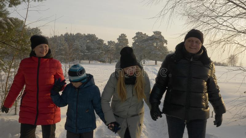 Friendly family walking in snowy forest at sunny winter day. Winter activity stock image