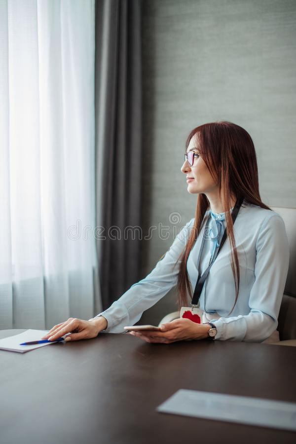 Friendly female boss gives a note to her assistant girl discussing tasks in the office. stock photography