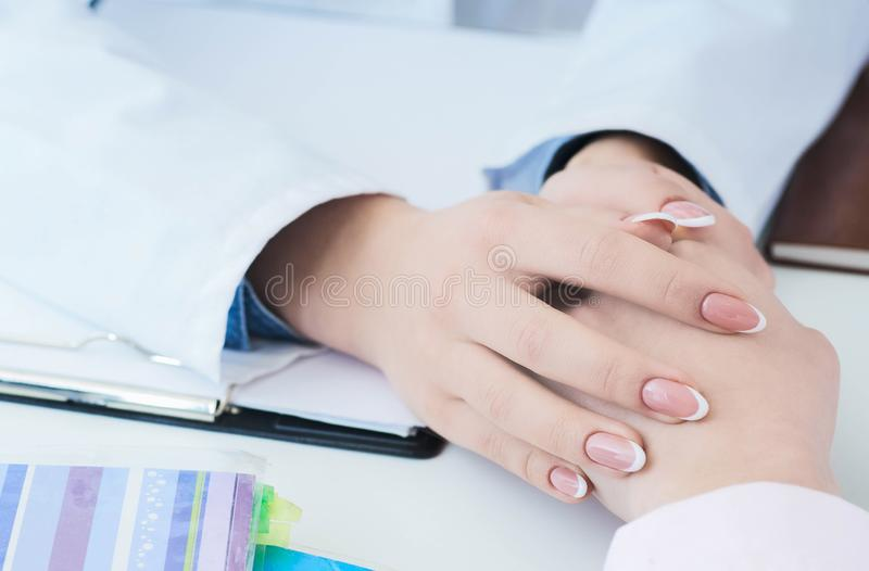 Friendly female doctor hands holding patient hand sitting at the desk for encouragement, empathy, cheering and support stock photos
