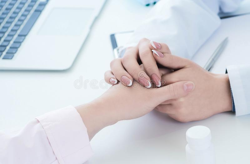 Friendly female doctor hands holding patient hand sitting at the desk for encouragement, empathy, cheering and support royalty free stock photography