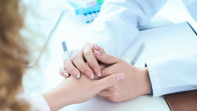 Friendly female doctor hands holding patient hand sitting at the desk for encouragement, empathy, cheering and support stock photography