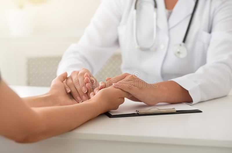 Friendly female doctor holding patient hands sitting at desk royalty free stock images