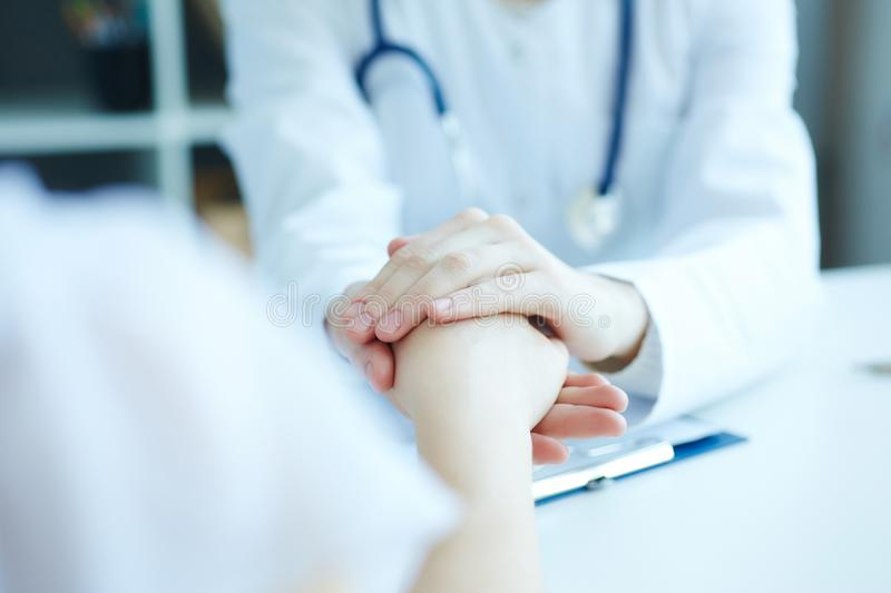 Friendly female doctor`s hands holding female patient`s hand for encouragement and empathy. royalty free stock photos